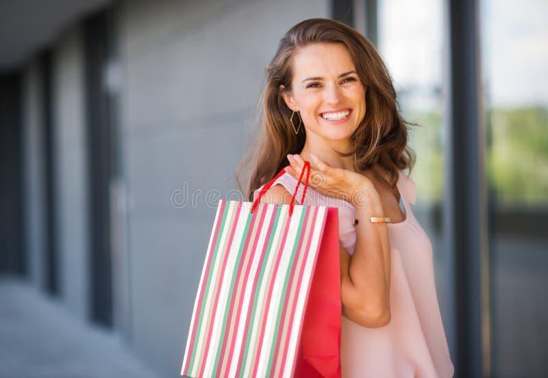特写镜头微笑,拿着stripey袋子的棕色毛发的妇女 库存图片