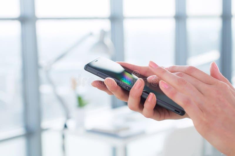 特写镜头拿着智能手机的女性手的侧视图图片,使用apps和Wi-Fi互联网,读消息 免版税库存照片
