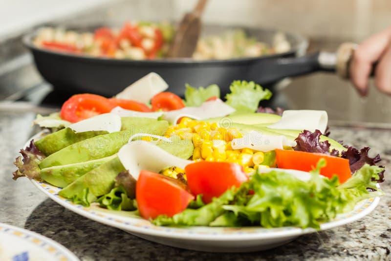 特写镜头新鲜的沙拉盘和女性烹调在平底锅 库存照片