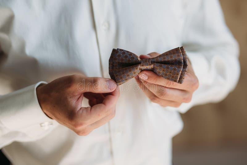 特写镜头有弓领带的新郎手 典雅的绅士clother、白色衬衣和棕色传送带 免版税库存照片