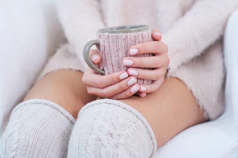 特写镜头有拿着杯子的桃红色修指甲的妇女手 库存图片