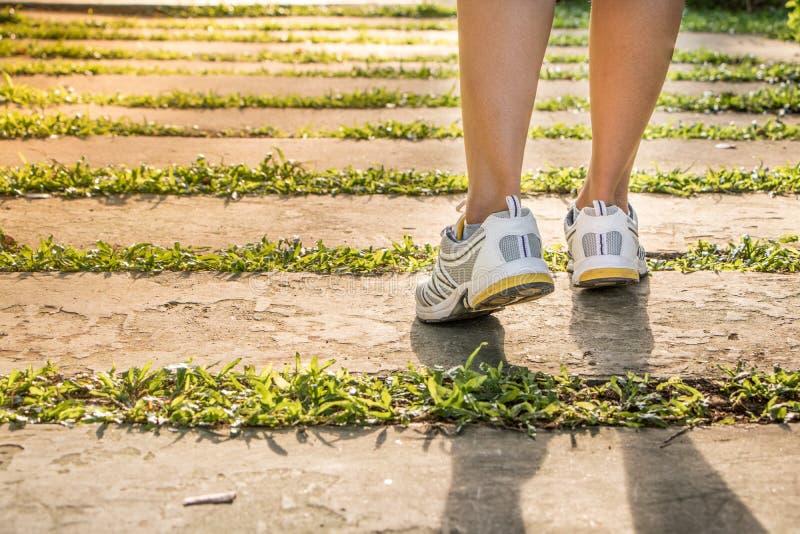 特写镜头概念英尺健身凹凸部跑腿者跑鞋日出健康妇女锻炼 免版税库存照片
