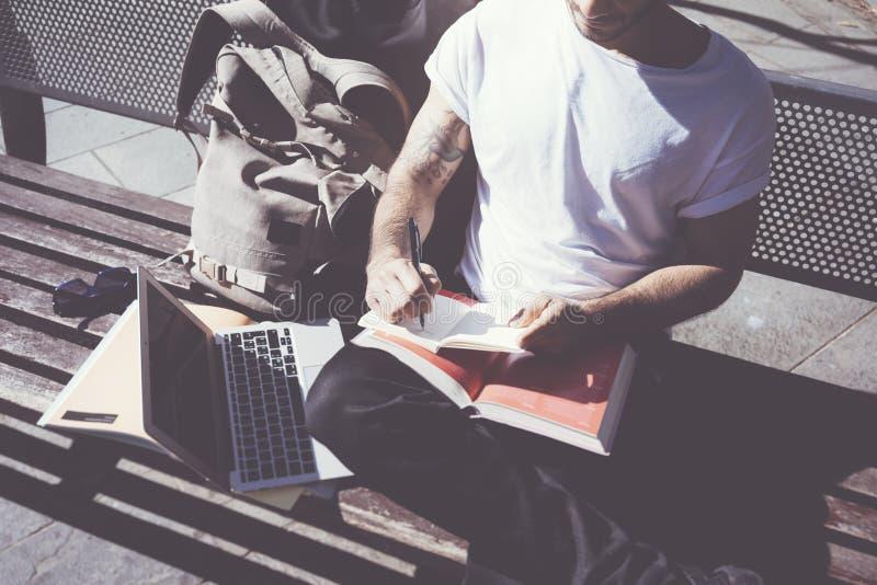 特写镜头照片人佩带的白色T恤杉坐的城市公园和书写笔记本 学习在大学,准备 免版税库存图片