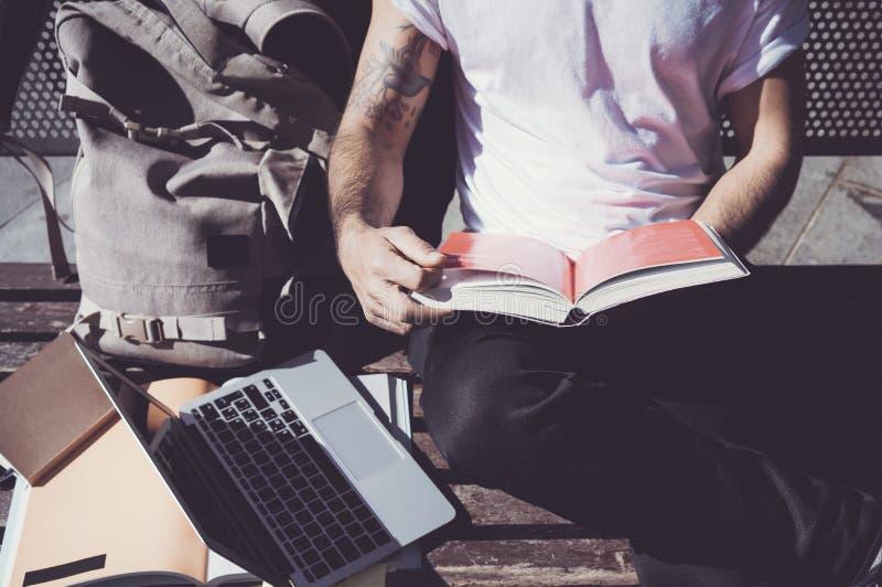 特写镜头照片人佩带的白色T恤杉坐的城市公园和阅读书 学习在大学,准备为 免版税图库摄影