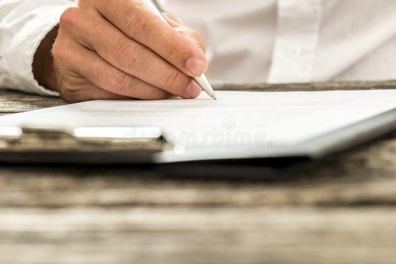 特写镜头男性手签署的订阅表单, l低角度视图  库存照片
