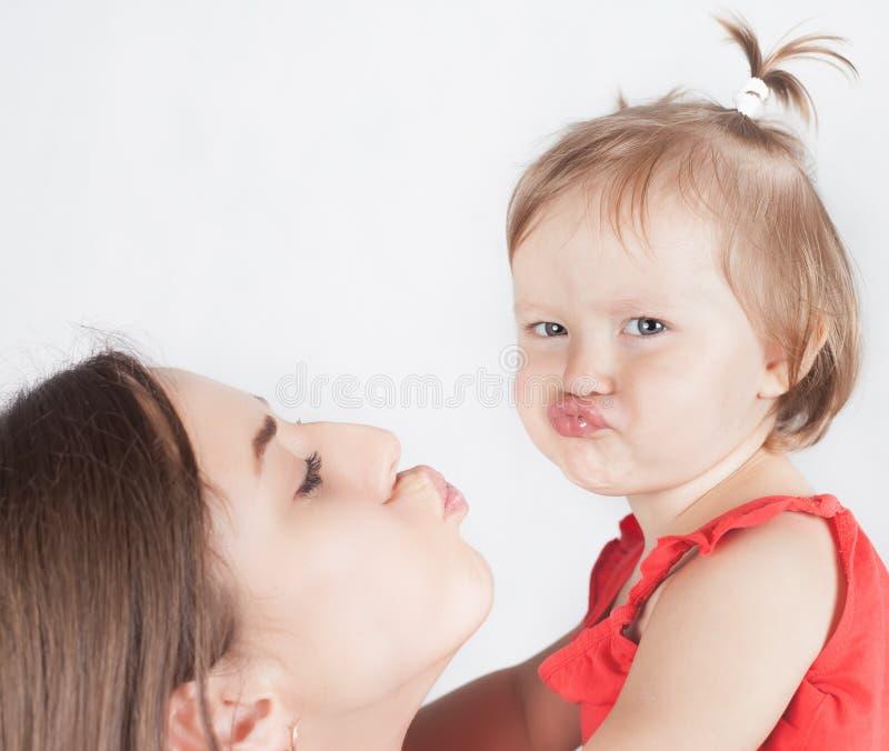 特写镜头滑稽的女婴和她的母亲白色背景的 免版税库存照片