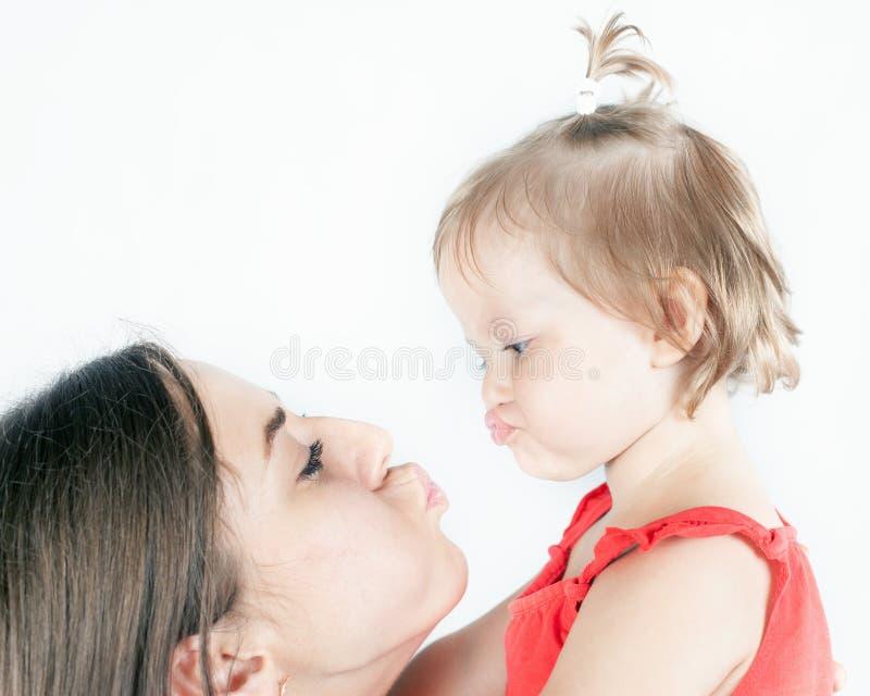 特写镜头滑稽的女婴和她的母亲白色背景的 库存图片