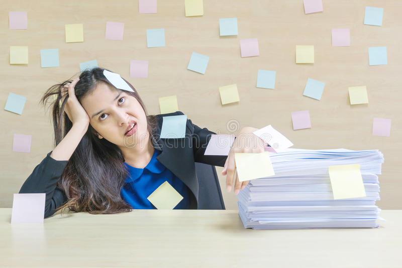特写镜头职业妇女从堆坚苦工作和工作证明书烦人在她前面在工作概念在被弄脏的木书桌上和 免版税库存照片