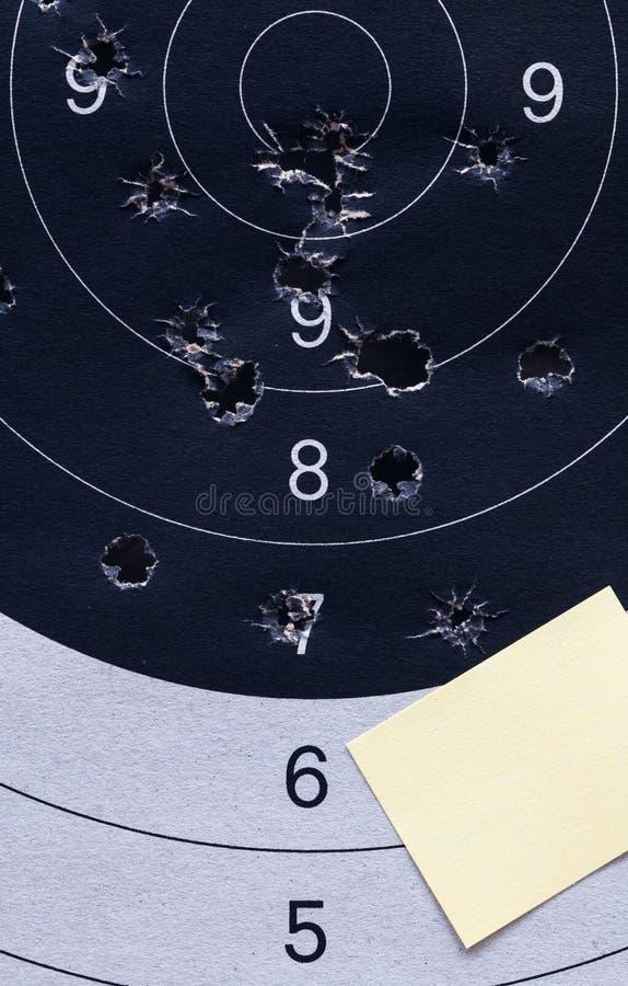特写镜头黄色便条纸板料 在黑白一个射击纸目标和靶心与弹孔 免版税库存图片