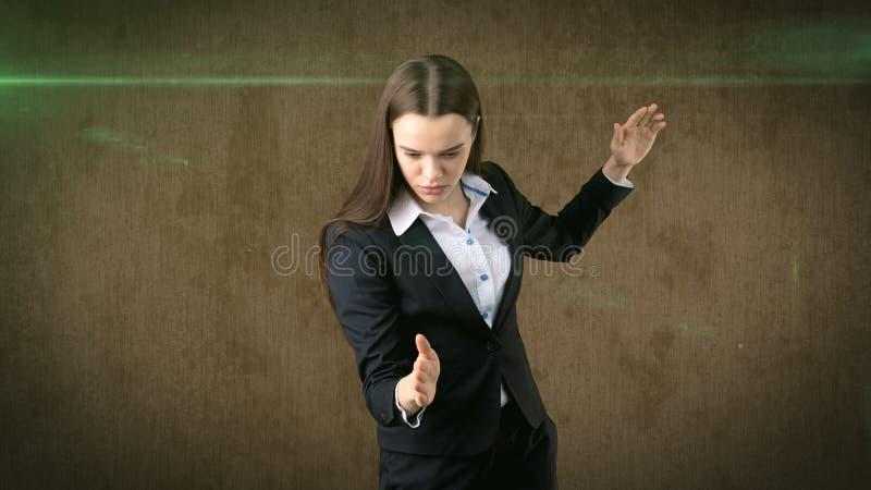 特写镜头画象举在空袭的女商人手与空手道剁,棕色背景 免版税库存图片
