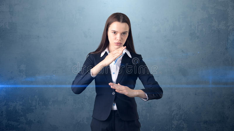 特写镜头画象举在空袭的女商人手与空手道剁,被隔绝的蓝色背景 库存照片