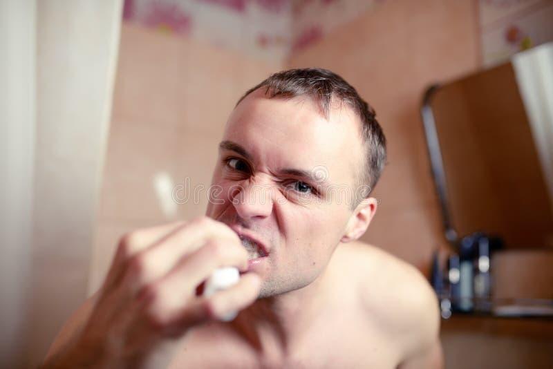 特写镜头画象人在卫生间里刷牙一副电刷子和鬼脸播放傻瓜 库存照片