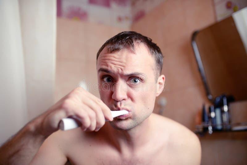 特写镜头画象人在卫生间里刷牙一副电刷子和鬼脸播放傻瓜 免版税库存图片