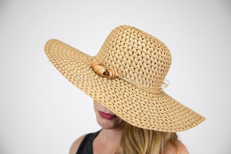 特写镜头画象成熟白肤金发的女性大帽子覆盖物眼睛 免版税库存图片