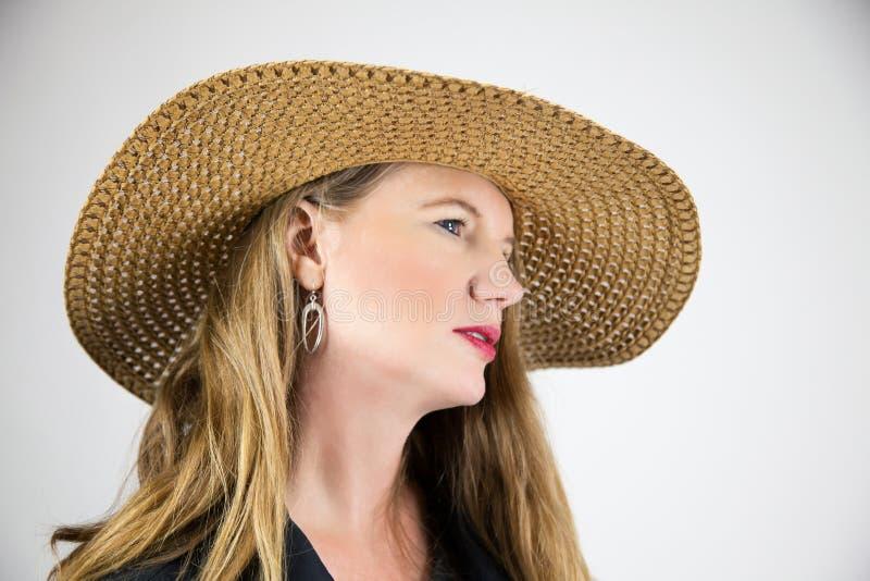 特写镜头画象成熟白肤金发的女性大帽子面孔被掀动远离照相机 库存照片