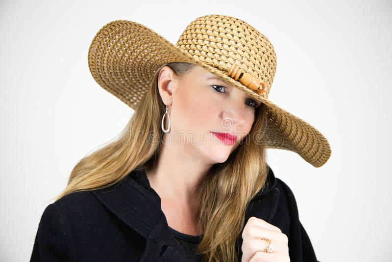 特写镜头画象成熟白肤金发的女性帽子和黑外套 免版税库存照片