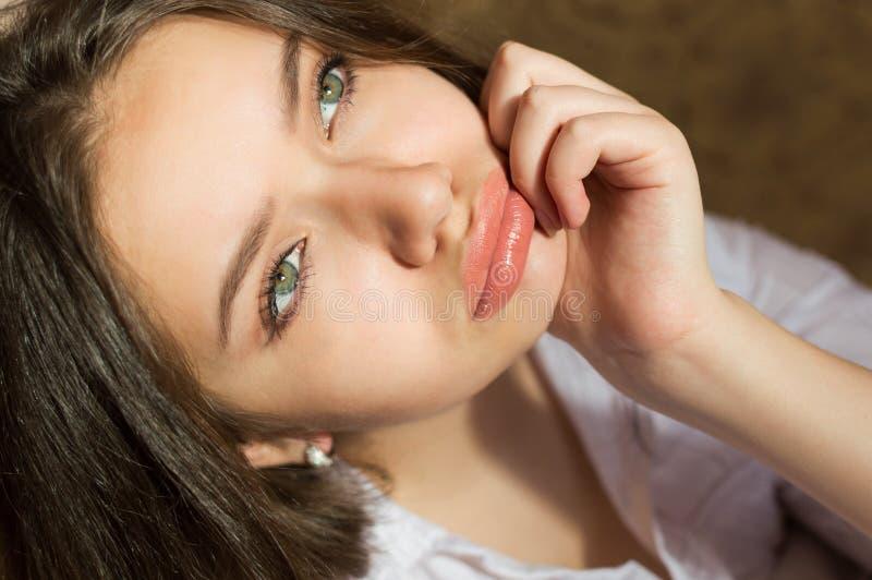 特写镜头迷人的女孩噘嘴的嘴唇和看 免版税库存照片