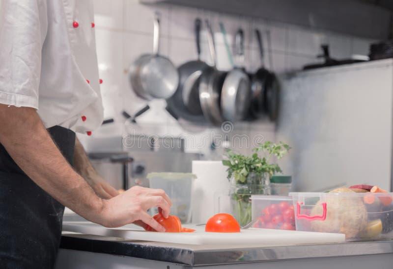 特写镜头递厨师厨房,切蕃茄 库存图片