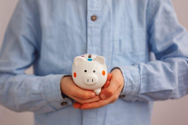 特写镜头递拿着一个存钱罐或钱箱的孩子 库存照片