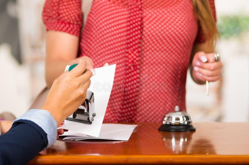 特写镜头顾客客人和互动在服务台,响铃的旅馆接待员坐桌,交换房间钥匙 免版税库存图片