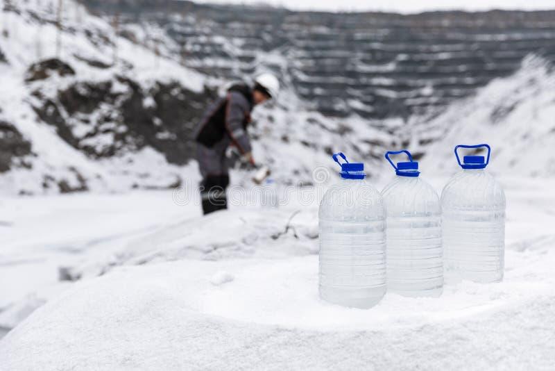特别衣裳的人采集水的样品潜在地沾染被毒性材料,在湖的冬天,  库存照片