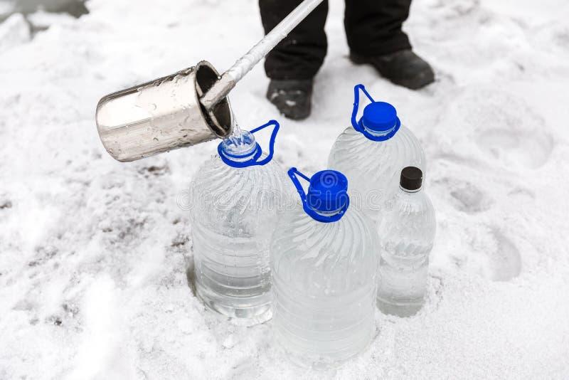 特别衣裳的人采集水的样品潜在地沾染被毒性材料,在湖的冬天,  免版税库存图片