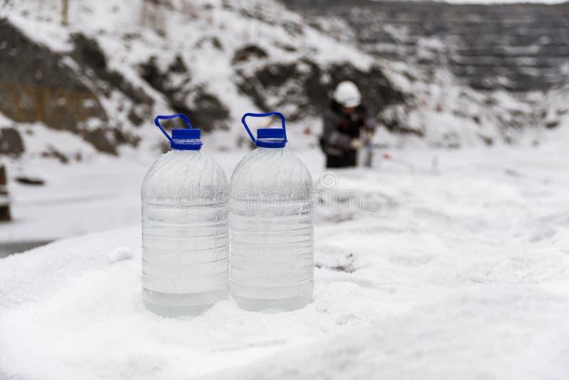特别衣裳的人采集水的样品潜在地沾染被毒性材料,在湖的冬天,  库存图片