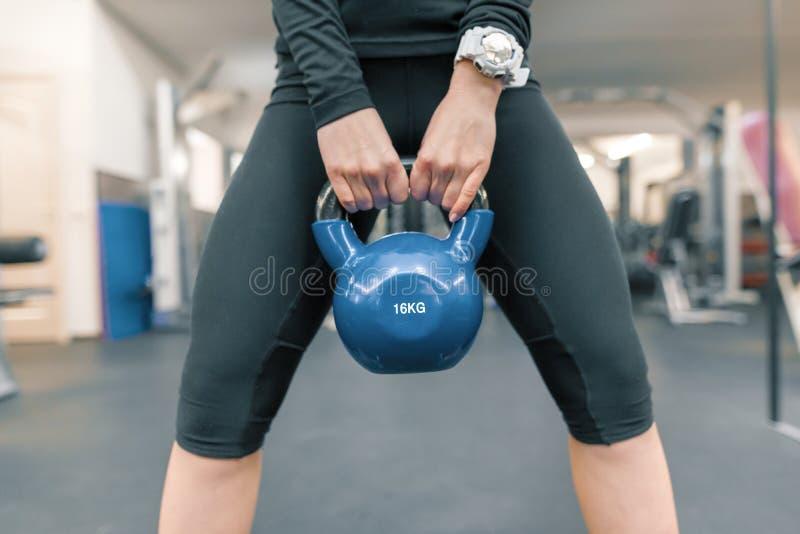 特别重的人在妇女关闭的手上,健身房背景 体育、健身、体型、训练、生活方式和人概念 免版税库存照片