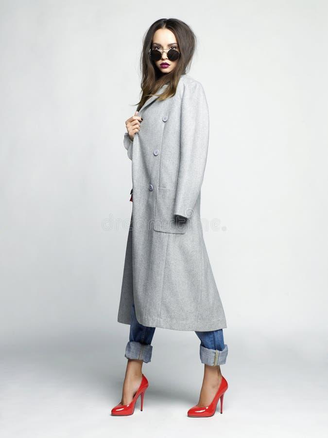 特大灰色外套的年轻时髦的妇女 免版税库存照片