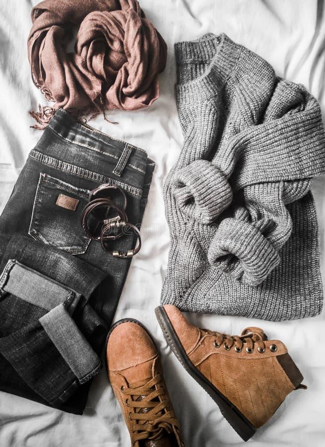 特大设置妇女的秋天、冬季衣服在轻的背景-牛仔裤,灰色的套头衫,绒面革褐色靴子和围巾 方式 库存照片