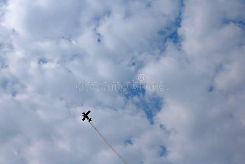 特技反对云彩的双翼飞机落后的烟 库存图片