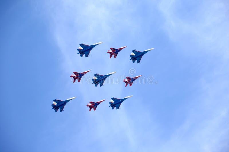 特技小组俄国骑士和Swifts在米格-29和苏-27战斗机在飞行中反对蓝天 免版税库存图片