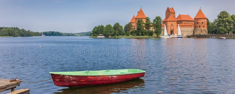 特拉凯城堡和一条红色和绿色小船全景在湖Galve 图库摄影