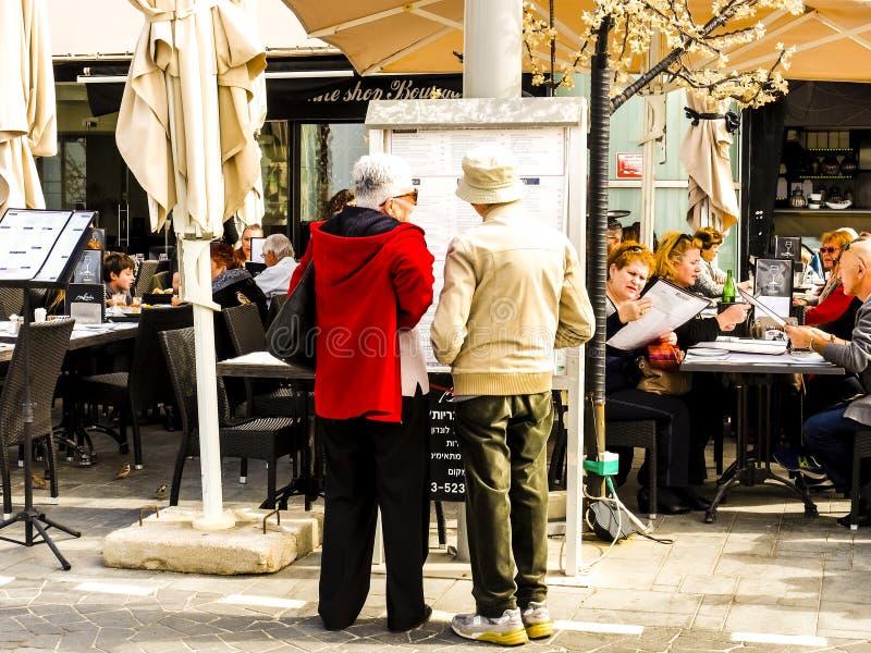 特拉维夫,以色列- 2017年2月4日:读餐馆菜单的年长夫妇 吃在室外咖啡馆的游人 库存照片