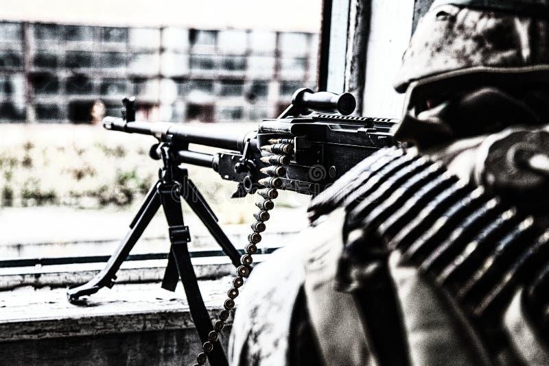 特攻队机械炮兵从窗口的战士生火 免版税库存照片