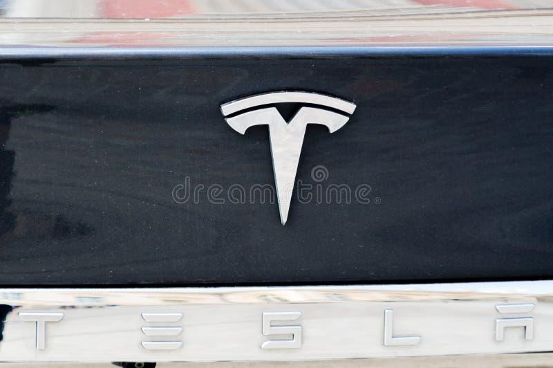 特斯拉开汽车在一辆黑汽车的商标 库存照片