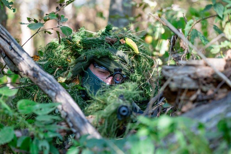 特种部队,战士有遏声器的,瞄准具攻击步枪 在等待在埋伏的盖子后 免版税库存照片