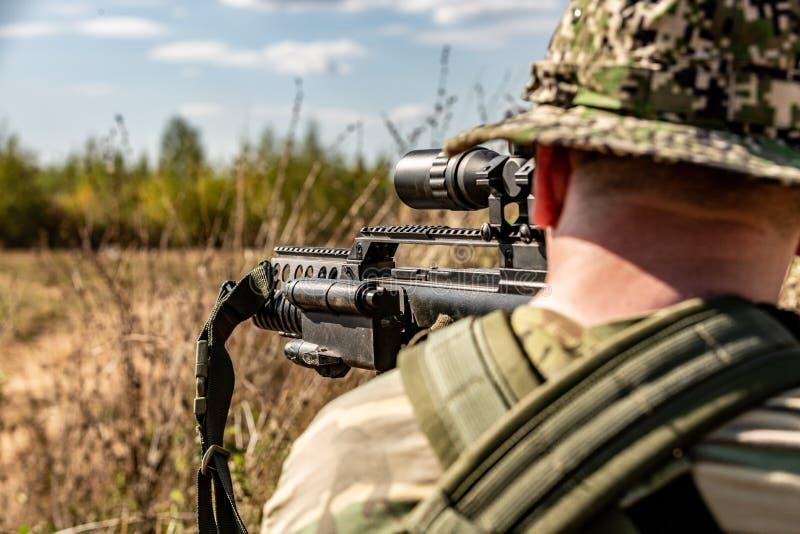 特种部队,战士有遏声器的,瞄准具攻击步枪 在等待在埋伏的盖子后 免版税图库摄影