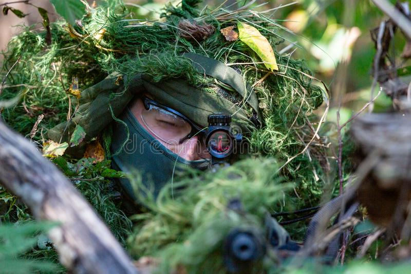 特种部队,战士有遏声器的,瞄准具攻击步枪 在等待在埋伏的盖子后 图库摄影