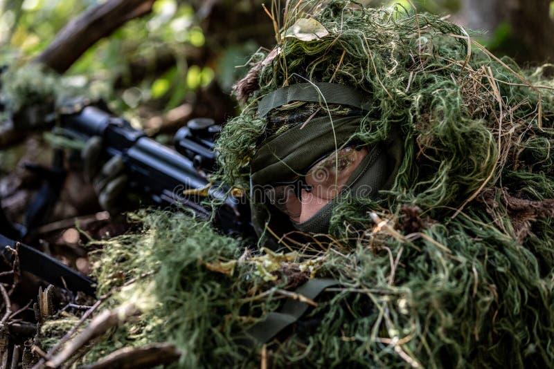 特种部队,战士有遏声器的,瞄准具攻击步枪 在等待在埋伏的盖子后 免版税库存图片