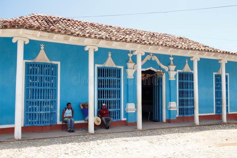 特立尼达,古巴-坐在一个蓝色房子前面的人们 库存图片