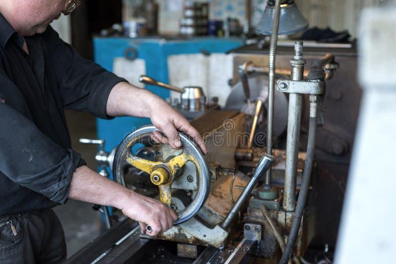 特纳起作用一台机械车床 转动的工作,处理通过切开的金属 免版税库存照片