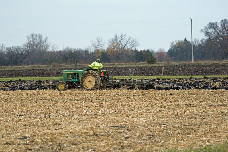 犁与一台老拖拉机的一块麦地 免版税库存照片