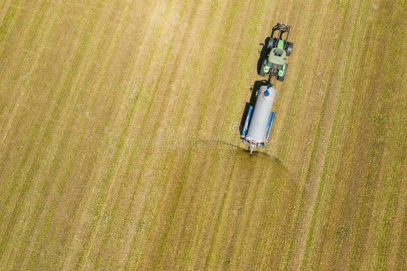 犁和喷洒在领域的农用拖拉机鸟瞰图 ?? o 照片夺取与寄生虫 库存照片