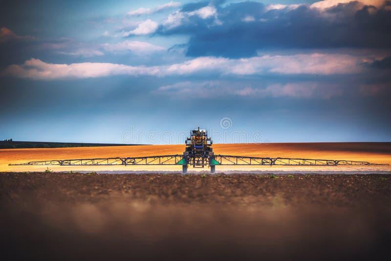 犁和喷洒在领域的农用拖拉机 免版税库存图片