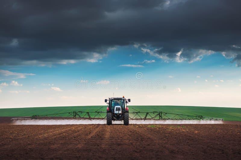犁和喷洒在领域的农用拖拉机 免版税库存照片