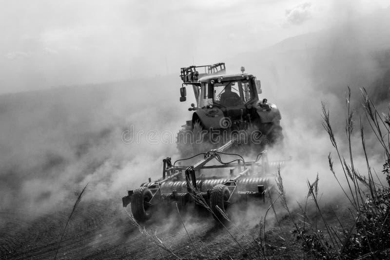 犁多灰尘的领域blach和白色的拖拉机 免版税库存照片