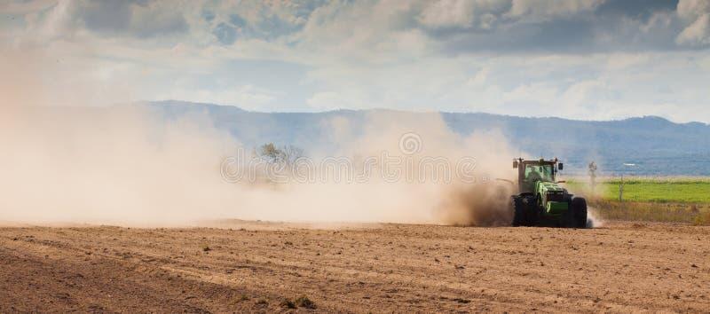 犁干燥农场土地的拖拉机 免版税图库摄影