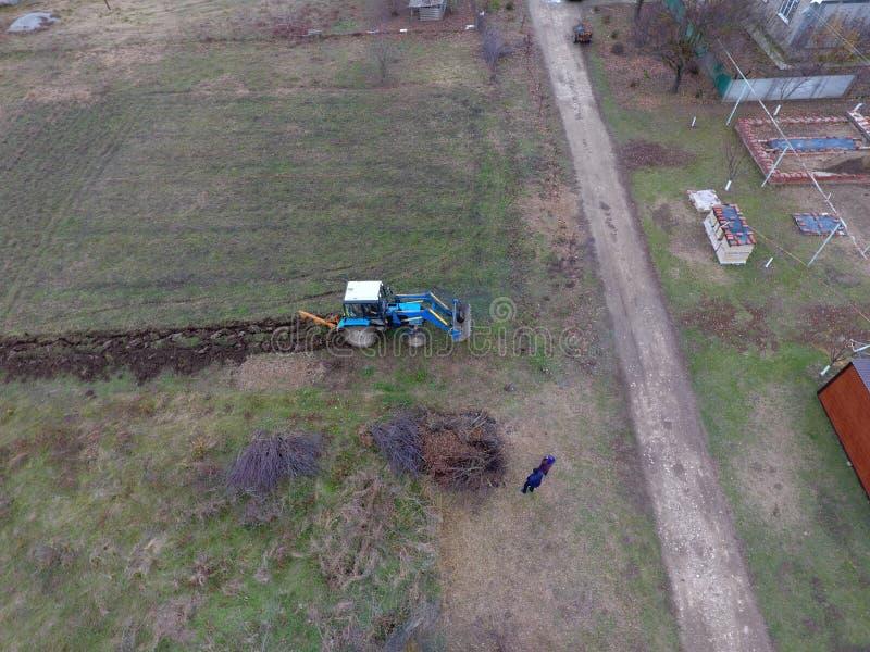 犁庭院的拖拉机 犁土壤在庭院里 免版税库存图片