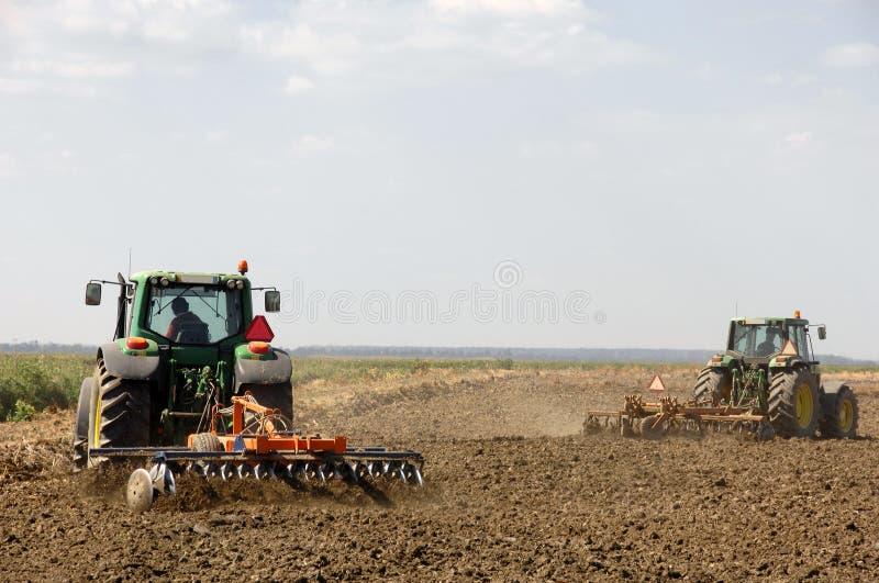 犁拖拉机的农夫 免版税图库摄影